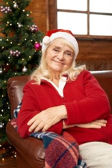 Donna anziana del colpo medio con la posa rossa del cappello