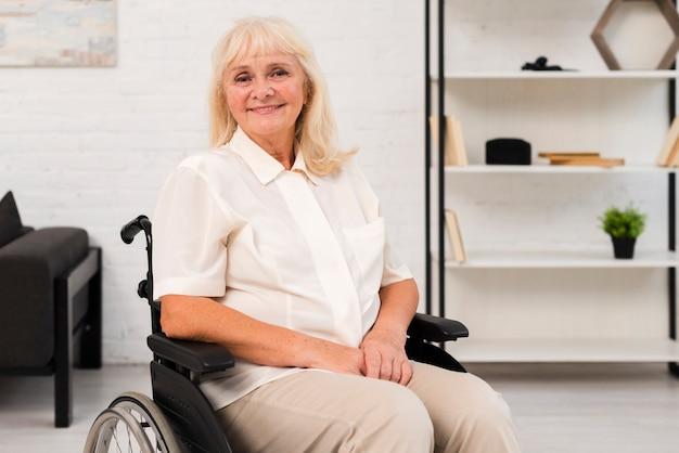 Donna anziana del tiro medio in sedia a rotelle che esamina la macchina fotografica