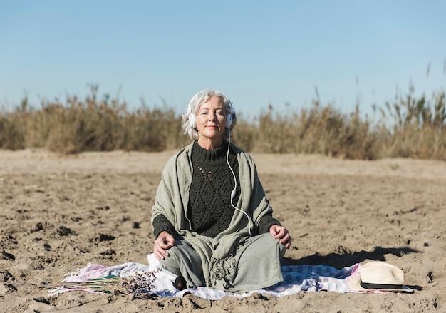 Donna anziana della foto a figura intera che medita all'aperto