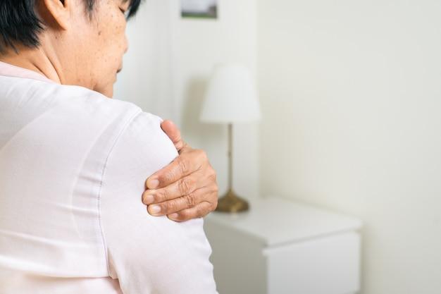 Donna anziana di dolore alla spalla che soffre dalla ferita al collo e alla spalla, problema di sanità del concetto senior