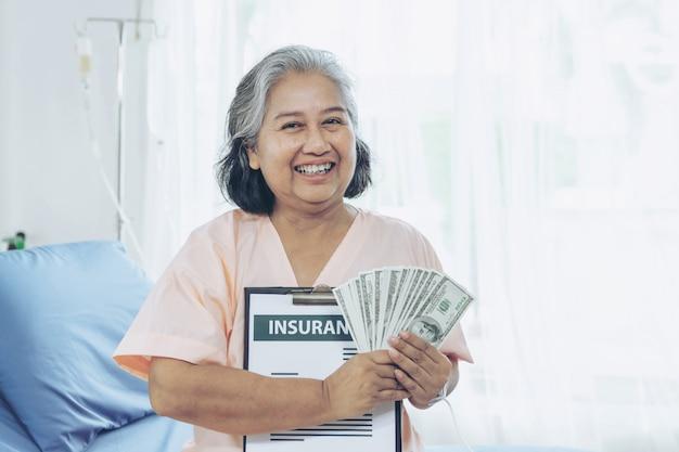 Donna anziana di lesioni dei pazienti sul letto del paziente in ospedale che tiene le banconote in dollari noi si sentono felici dall'ottenere i soldi dell'assicurazione dalle compagnie di assicurazione