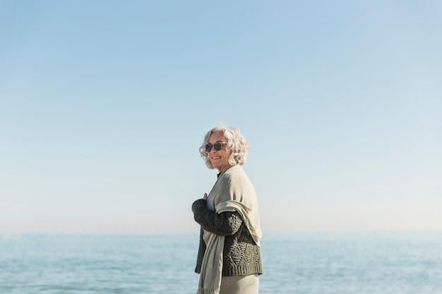 Donna anziana di smiley del colpo medio sulla spiaggia