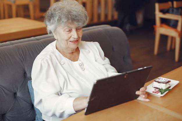 Donna anziana elegante che si siede in un caffè e che per mezzo di un computer portatile
