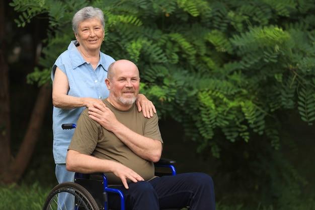 Donna anziana felice che cammina con uomo anziano disabile seduto in sedia a rotelle all'aperto