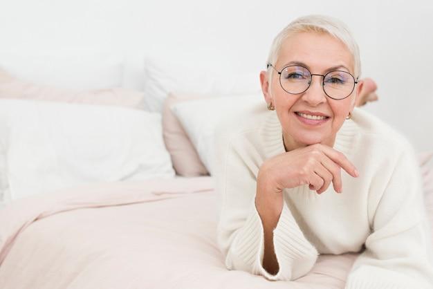 Donna anziana felice che posa a letto con lo spazio della copia