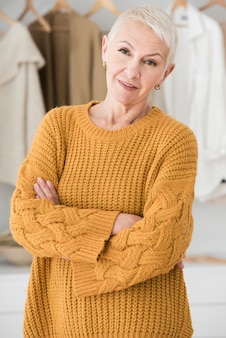 Donna anziana in posa con le braccia incrociate e sorridente
