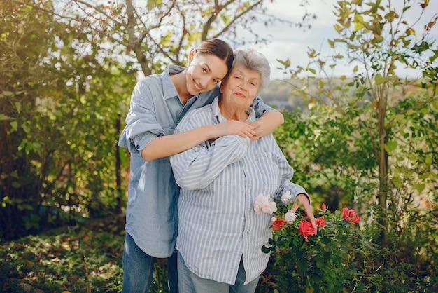Donna anziana in un giardino con la giovane nipote