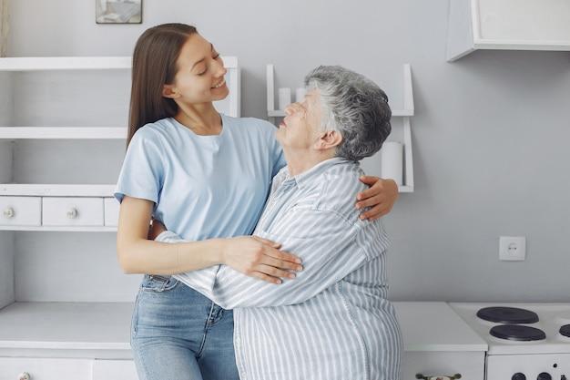 Donna anziana in una cucina con la giovane nipote