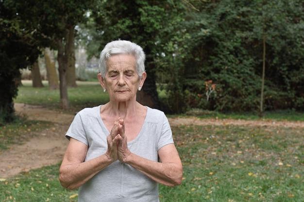 Donna anziana praticando yoga all'aperto
