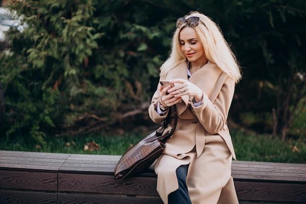 Donna anziana seduta su una panchina nel parco e parlando al telefono