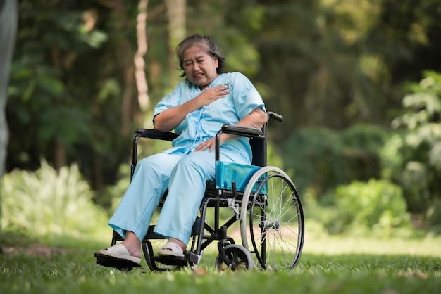 Donna anziana sola che si siede sensibilità triste sulla sedia a rotelle al giardino in ospedale