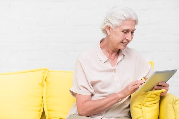 Donna anziana sorridente che si siede sul sofà facendo uso della compressa digitale
