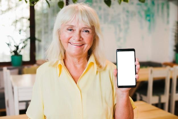 Donna anziana sorridente emozionante che mostra smartphone alla macchina fotografica