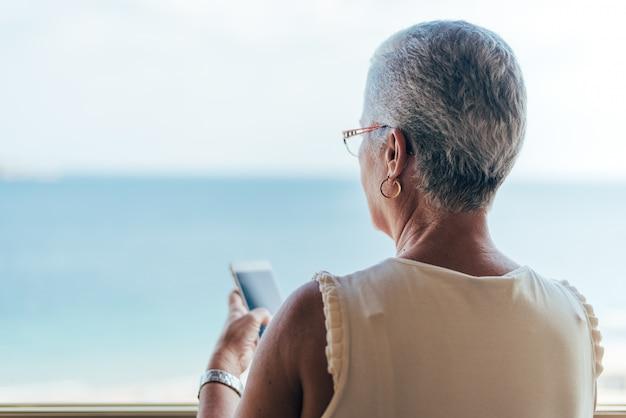 Donna anziana sul telefono cellulare a casa
