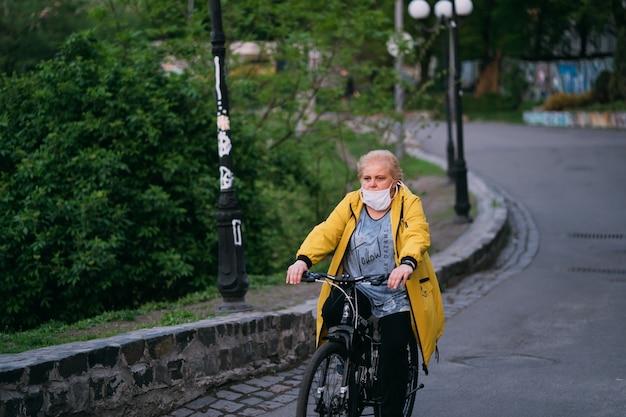 Donna anziana sulla sua bici con una maschera chirurgica in strada