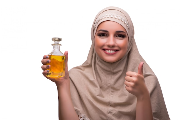 Donna araba con la bottiglia di profumo isolata su bianco