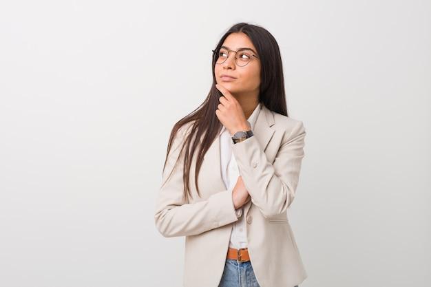 Donna araba di giovani affari isolata contro una parete bianca che guarda lateralmente con espressione dubbiosa e scettica.