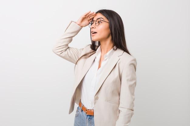 Donna araba di giovani affari isolata contro una parete bianca che guarda lontano tenendo la mano sulla fronte.