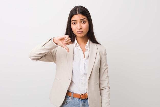 Donna araba di giovani affari isolata contro una parete bianca che mostra un gesto di avversione, pollici giù. concetto di disaccordo.