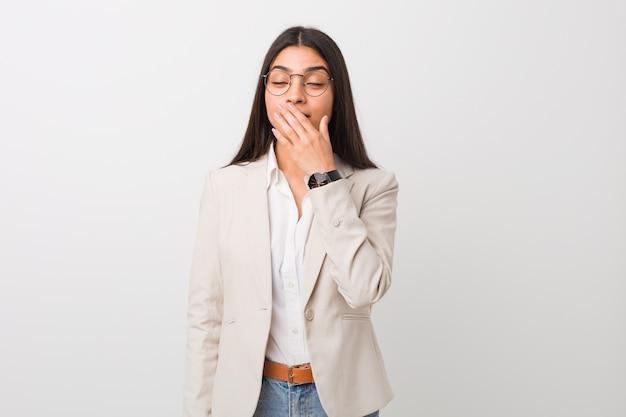 Donna araba di giovani affari isolata contro una parete bianca che sbadiglia mostrando un gesto stanco che copre la bocca di mano.