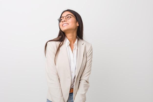 Donna araba di giovani affari isolata contro una parete bianca che sogna di raggiungere gli scopi e gli scopi