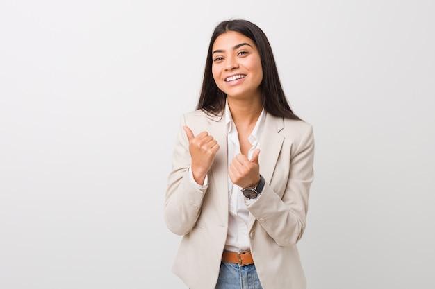 Donna araba di giovani affari isolata contro una priorità bassa bianca che alza entrambi i pollici in su, sorridendo e sicuro.