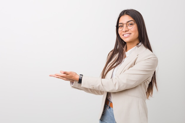 Donna araba di giovani affari isolata contro una priorità bassa bianca che tiene uno spazio della copia su una palma.