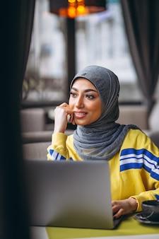 Donna araba in hijab all'interno di un caffè che lavora al computer portatile