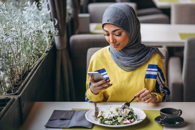 Donna araba in hijab all'interno di un caffè che mangia insalata