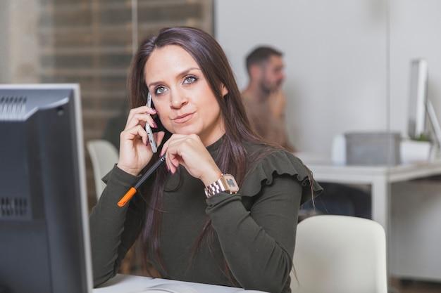 Donna arrabbiata che comunica sul telefono in ufficio