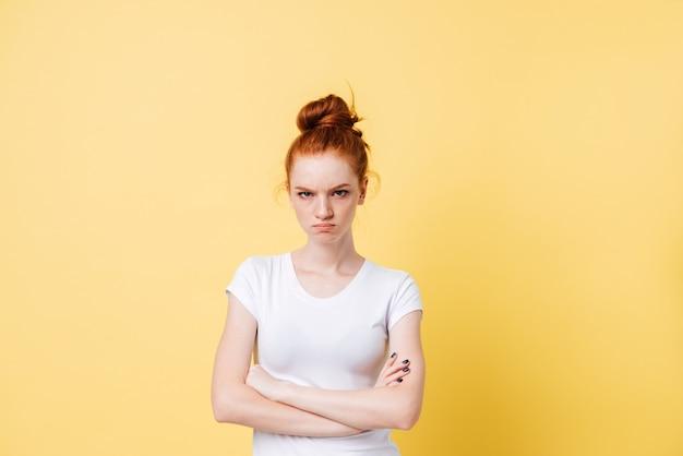 Donna arrabbiata dello zenzero che posa con le braccia attraversate