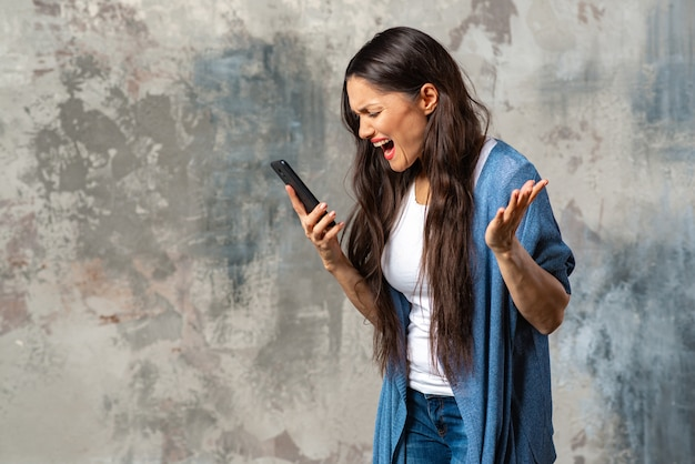 Donna arrabbiata guardando lo schermo dello smartphone e urlando.