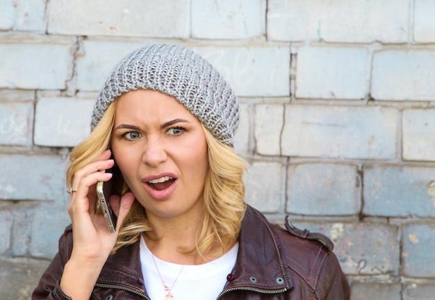 Donna arrabbiata infelice del ritratto che parla sul telefono cellulare che sembra frustrato