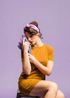 Donna artistica che si siede e che abbraccia i fiori della lavanda
