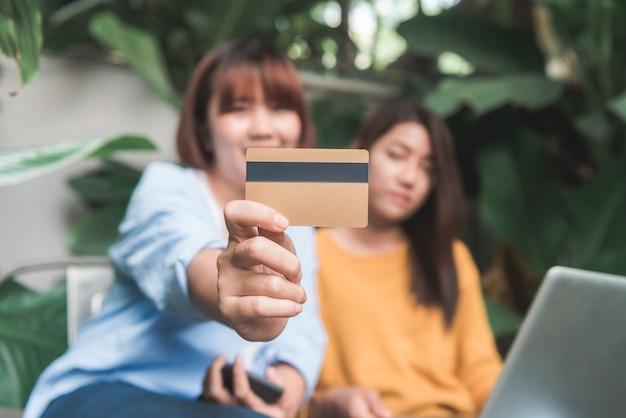 Donna asia shopping online utilizzando la carta di credito con computer tablet al bar ristorante, concetto di stile di vita digitale, mobile banking,