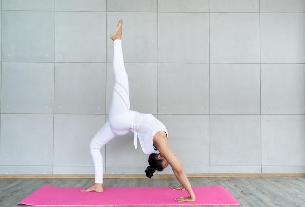 Donna asiatica adulta che fa un esercizio di yoga nella stanza di esercizio nella sua casa.