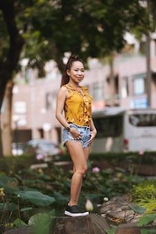 Donna asiatica alla moda vestita adatta dei giovani in pantaloncini e blusa luminosa che posa in via urbana