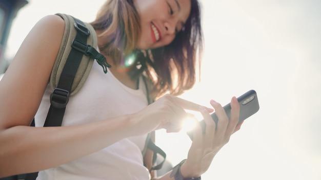 Donna asiatica allegra di blogger di viaggiatore con zaino e sacco a pelo che per mezzo dello smartphone per la direzione e che considera la mappa di posizione