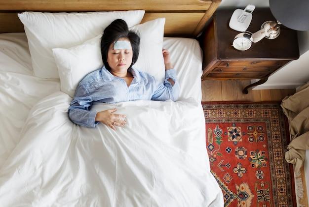 Donna asiatica ammalata con febbre che dorme sul letto
