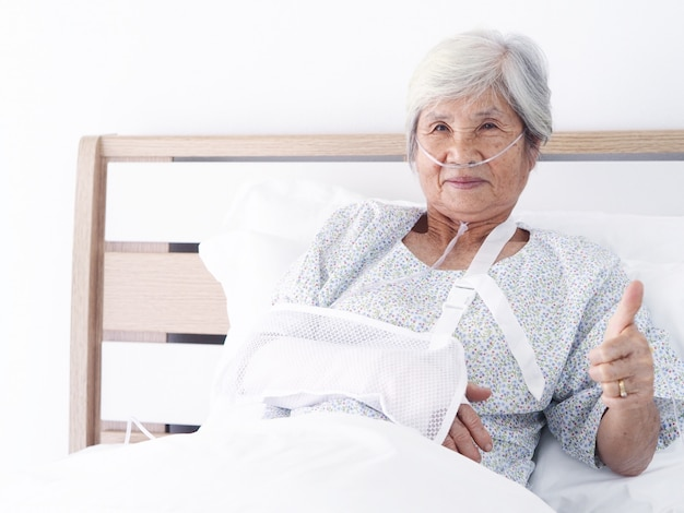 Donna asiatica anziana che mette su letto nella stanza di ospedale.
