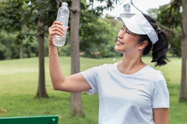 Donna asiatica anziana che sorride bevendo acqua dolce di estate al parco.