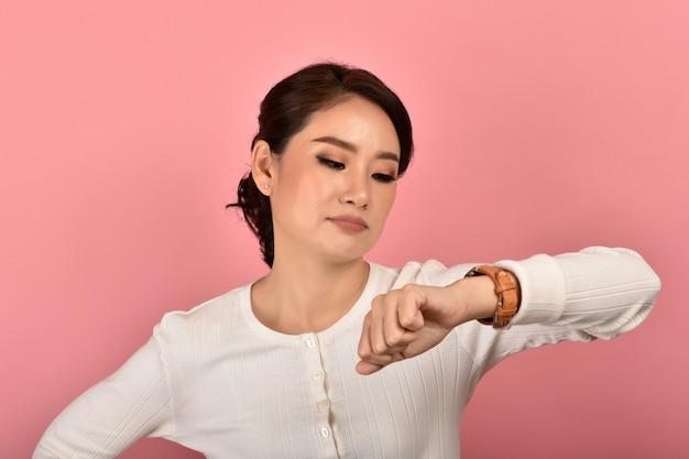 Donna asiatica arrabbiata e turbata che aspetta qualcuno, donna che esamina l'orologio infastidito per l'appuntamento ritardato, responsabilità di tempo.
