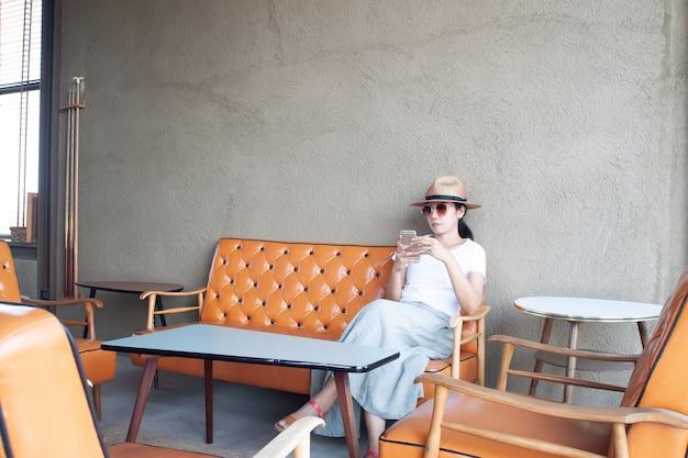 Donna asiatica astuta 40+ che utilizza telefono cellulare nel caffè. stile di vita e tecnologia