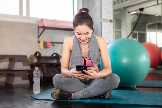 Donna asiatica astuta in telefono della tenuta degli abiti sportivi alla palestra di forma fisica.