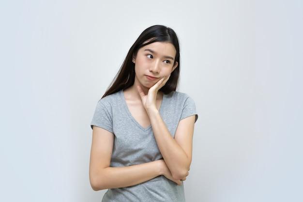Donna asiatica attraente che pensa isolato, bella ragazza asiatica