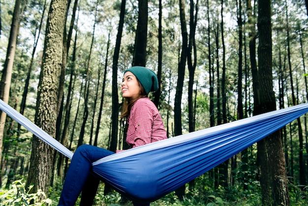 Donna asiatica attraente del viaggiatore che si siede in hammock
