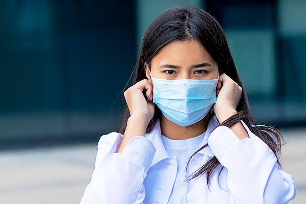 Donna asiatica, attraente ragazza etnica che indossa una maschera medica sul viso, guardando la telecamera con uno sguardo serio in una camicia bianca fuori dal centro commerciale.