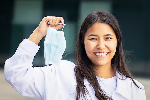 Donna asiatica, attraente ragazza etnica si toglie la mascherina medica dal viso, felice con un sorriso guarda la telecamera. in una camicia bianca fuori dal centro commerciale. si tolse la maschera