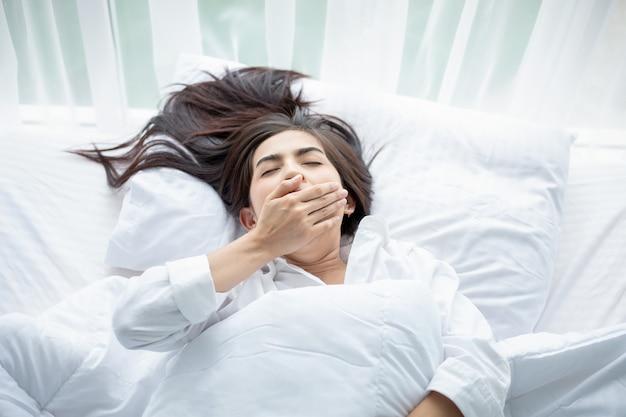 Donna asiatica bella giovane donna sorridente che si siede e dorme nel letto bianco e che si estende al mattino in camera da letto dopo essersi svegliata nel suo letto completamente riposato