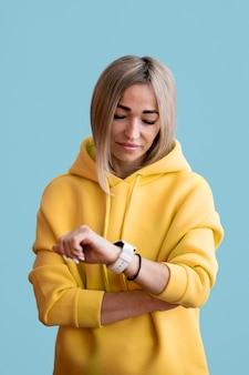 Donna asiatica bionda che esamina il suo orologio astuto
